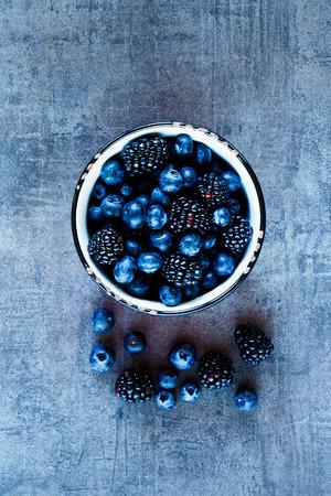 Fresh dark berries in vintage mug over rustic background, top view.