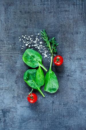 Healthy food background with fresh vegetarian ingredients (spinach, tomatoes, grey salt and herbs) on dark vintage table, top view.