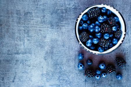 Organic fresh dark berries in vintage mug over rustic background with space for text, top view.