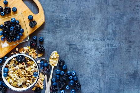 Hoogste mening van smakelijke ontbijtlijst met granola in uitstekende kom en donkere bessen op grungeachtergrond. Kopieer de ruimte aan de rechterkant.