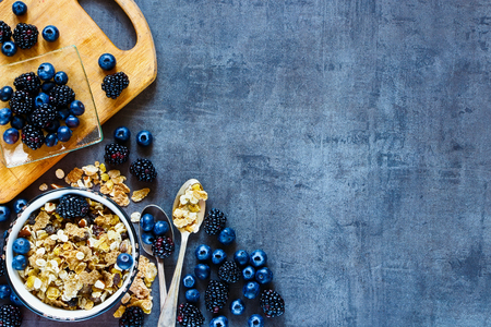 Top view of tasty breakfast table with granola in vintage bowl and dark berries on grunge background. Copy space on right. Stock Photo