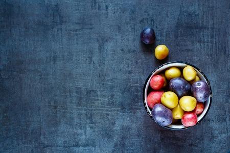 papas: Alimentación de fondo con variedades mixtas de patatas frescas en un tazón sobre la mesa de la vendimia del grunge oscuro. Vista superior. Foto de archivo