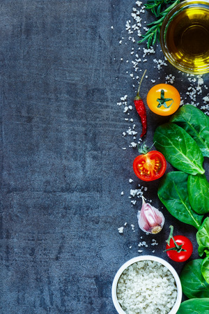 Vegetarian ingredients (spinach, tomatoes, olive oil, salt and herbs) on dark vintage table, top view. Background layout with free text space. Stock Photo
