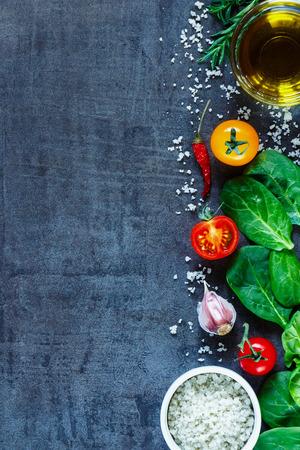 Vegetarische ingrediënten (spinazie, tomaten, olijfolie, zout en kruiden) op donkere vintage tafel, bovenaanzicht. Achtergrondlay-out met vrije tekstruimte.