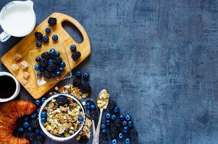 Rustic breakfast table with granola in vintage bowl, dark berries, cup of coffee and croissants on grunge background. Copy space, top view.