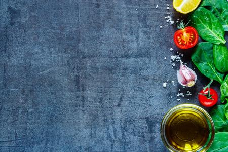 Close-up van diverse vegetarische ingrediënten (spinazie, tomaten, olijfolie, kruiden en specerijen) op een donkere vintage tafel, bovenaanzicht.