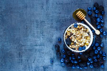 Granola im Vintage-Becher, dunkle Beeren und Honig für leckeres Frühstück auf Grunge Hintergrund mit Platz für Text auf der linken, Draufsicht.