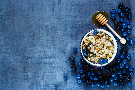 snack food: Granola in vintage mug, dark berries and honey for delicious breakfast on grunge background with space for text on left, top view. Stock Photo