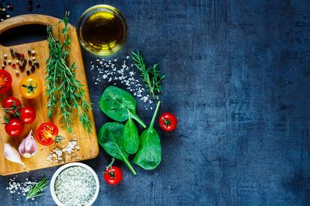 Biologische vegetarische ingrediënten, olijfolie en kruiden op rustieke houten snijplank over donkere vintage achtergrond met ruimte voor tekst, bovenaanzicht.