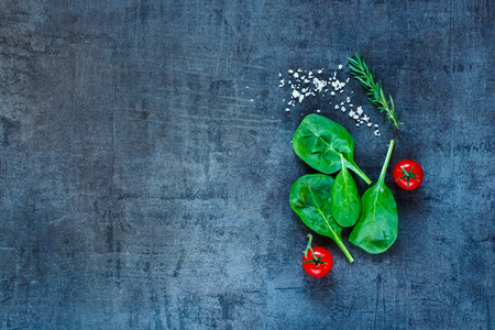 Verse vegetarische ingrediënten (spinazie, tomaten, grijs zout en kruiden) op donkere vintage tafel, bovenaanzicht. Achtergrondlay-out met vrije tekstruimte.
