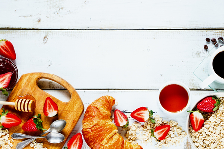 Delicious rural breakfast with oats, fresh strawberries, cup of coffee, fruity jam, honey and croissant on rustic white wooden background with space for text. Top view.