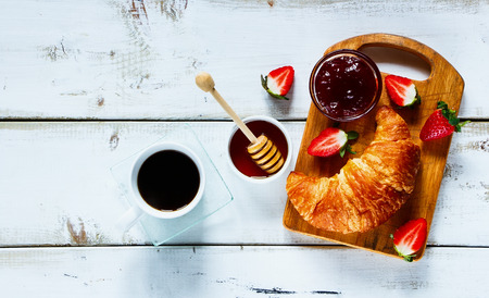 Top view of rural breakfast with cup of coffee, croissant, jam, honey and strawberries on rustic white wooden table. Background layout with free text space.