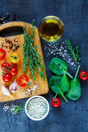 健康的な有機ベジタリアン食材、オリーブ オイルと背景を食べて、素朴な木製のまな板、上面の調味料。 写真素材