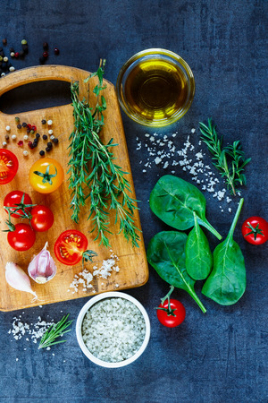 Healthy eating background with organic vegetarian ingredients, olive oil and seasoning on rustic wooden cutting board, top view. Фото со стока