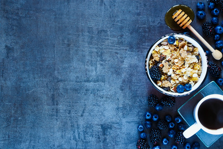 Tasty granola in vintage mug, dark berries, coffee and honey for delicious breakfast on grunge background with space for text on left, top view.