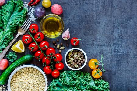 新鮮な美味しい野菜やヴィンテージの暗い背景、平面図、国境のおいしい料理の食材と生玄米。 写真素材