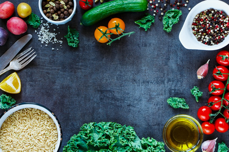 Brown rice with fresh delicious vegetables and ingredients for tasty cooking on vintage dark background, top view.