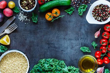 Bruine rijst met heerlijke verse groenten en ingrediënten voor lekker koken op vintage donkere achtergrond, bovenaanzicht.