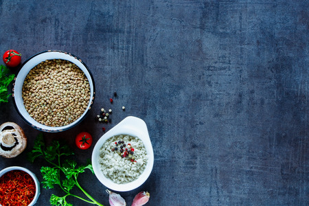 Top view of green lentils with various colorful spices and vegetables on dark grunge table. Background layout with free text space.