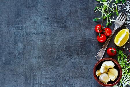 暗い古い背景に (トマト、ニンニク、唐辛子、レモン、サラダの葉、オリーブ、オリーブ オイル) を料理の食材の平面図です。