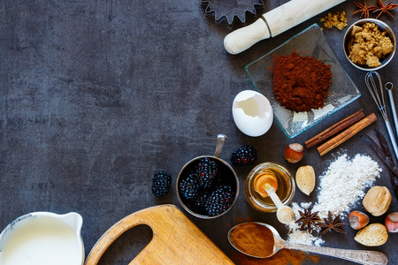 Assortment of ingredients and tools for baking cake (whole flour, honey, nuts, yolk, cacao powder and spices) on dark vintage table, top view.