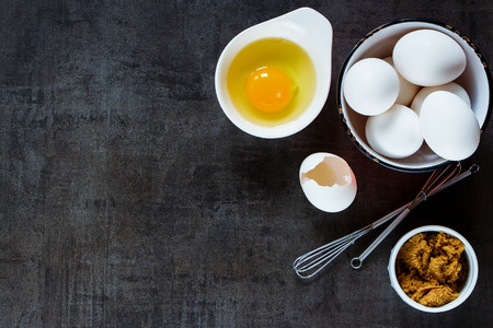 Ingredients background: fresh eggs and brown sugar with whisk for baking on dark vintage table, top view, copy-space.