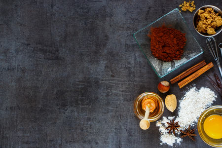 table top: Various ingredients for baking cake (whole flour, honey, nuts, yolk, cacao powder and spices) on dark vintage table, top view. Stock Photo