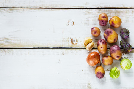 text space: Organic vegetables on white wooden background with space for text, top view.