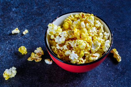 bowl of popcorn: Old ceramic bowl with salt popcorn on stone background, selective focus. Stock Photo
