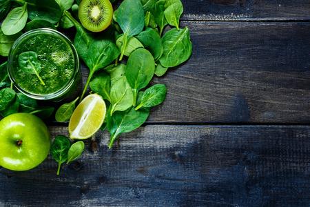 素朴な木製の背景に jar の緑の果物と野菜の健康的なスムージーのクローズ アップ。フリー テキスト スペースの背景のレイアウト。平面図です。
