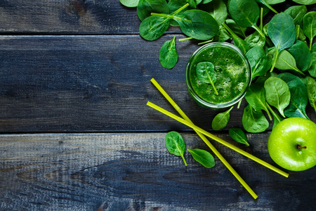 spinach: Healthy smoothie with green fruits and vegetables in a jar on rustic wooden background. Background layout with free text space. Top view.