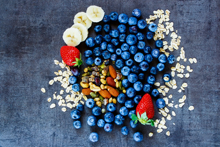 bio food: Healthy ingredients (oat flakes, berries with yogurt and seeds) for breakfast or smoothie on dark vintage background Stock Photo