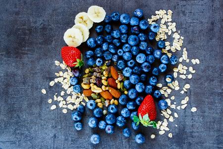 plato de comida: ingredientes sanos (copos de avena, bayas con yogur y semillas) para el desayuno o un batido en el fondo de la vendimia oscura
