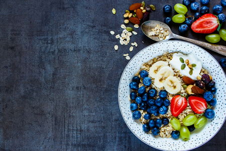 Food background with plate of oat flakes, berries with yogurt and seeds for tasty breakfast on dark vintage board Stock Photo