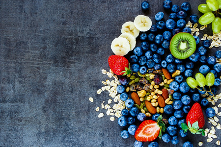 Fresh healthy ingredients (oat flakes, green grapes, banana, berries with yogurt and seeds) for breakfast or smoothie on dark vintage background