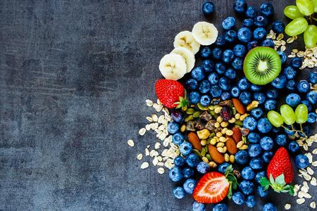 licuado de platano: Los ingredientes frescos sanos (copos de avena, uvas verdes, plátano, bayas con yogur y semillas) para el desayuno o un batido en el fondo de la vendimia oscura Foto de archivo