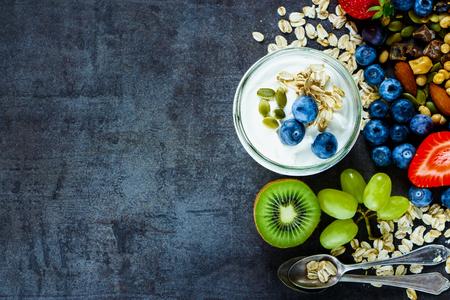 prima colazione: Primo piano di ingredienti gustosi (fiocchi di avena, uva verde, kiwi, frutti di bosco con yogurt e semi) per la colazione o frullato su sfondo scuro epoca