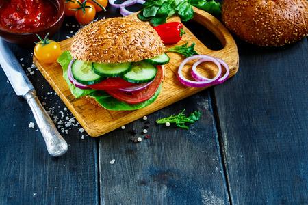 어두운 소박한 나무 테이블, 선택적 포커스에 신선한 야채와 함께 맛있는 채식 햄버거.