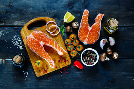 healthy foods: Two steaks of salmon with fresh ingredients for tasty cooking on rustic wooden background, top view, banner.