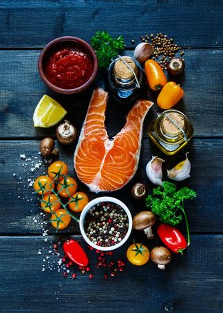 素朴な木製の背景、平面図、バナーにおいしい料理に新鮮な食材とサーモンの生のステーキ。