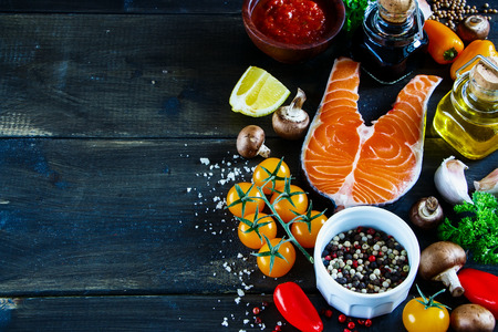 Close up of salmon steak with fresh ingredients for tasty cooking on rustic wooden background, selective focus, banner. Stock Photo