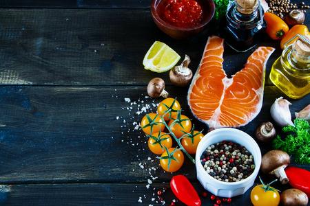 Ciérrese para arriba del filete de color salmón con los ingredientes frescos para cocinar sabroso en el fondo de madera rústico, foco selectivo, bandera.