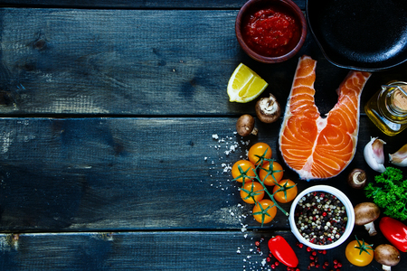 Steak of salmon with fresh ingredients for tasty cooking on rustic wooden background, top view, banner. Stock Photo