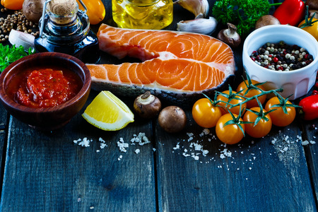 Close up of tasty fresh salmon steak with ingredients for cooking on rustic wooden background, selective focus, banner.