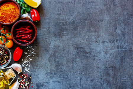 Dry colorful spices in bowls with fresh seasoning and healthy vegetables on dark rustic background, top view, border.