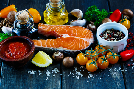 Close up of fresh salmon steak with ingredients for tasty cooking on rustic wooden background, selective focus, banner.