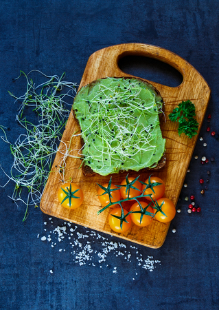 medicago: Top view of fresh vegetarian sandwich with whole grain bread, alfalfa and guacamole on rustic wooden cutting board over dark vintage background.