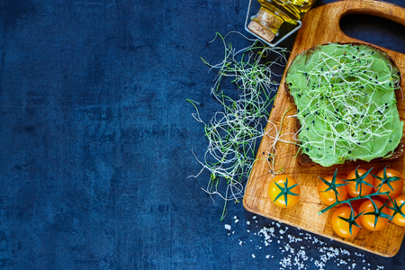 medicago: Delicious vegetarian sandwich with whole grain bread, alfalfa and guacamole on rustic wooden cutting board over dark vintage table, top view. Stock Photo