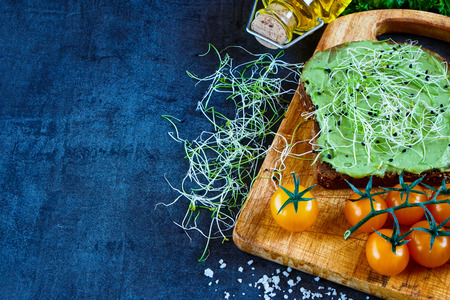 medicago: Delicious vegetarian sandwich with whole grain bread, alfalfa and guacamole on rustic wooden cutting board over dark vintage table, selective focus. Stock Photo