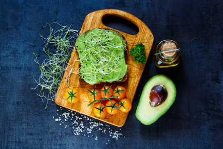 medicago: Fresh vegetarian sandwich with whole grain bread, alfalfa and guacamole on rustic wooden cutting board over dark vintage background, top view.